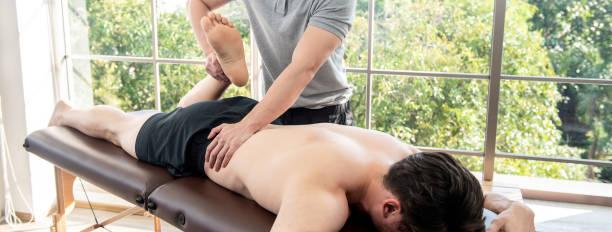 fisioterapeuta dando masaje y estiramiento a paciente masculino en clínica - masaje deportivo fotografías e imágenes de stock