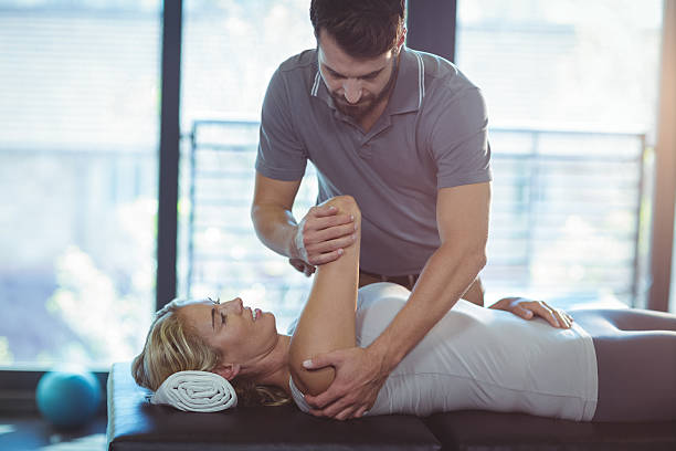 Physiotherapist giving shoulder therapy to a woman stock photo