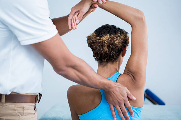physiotherapist giving shoulder therapy to a woman - sports medicine stock photos and pictures