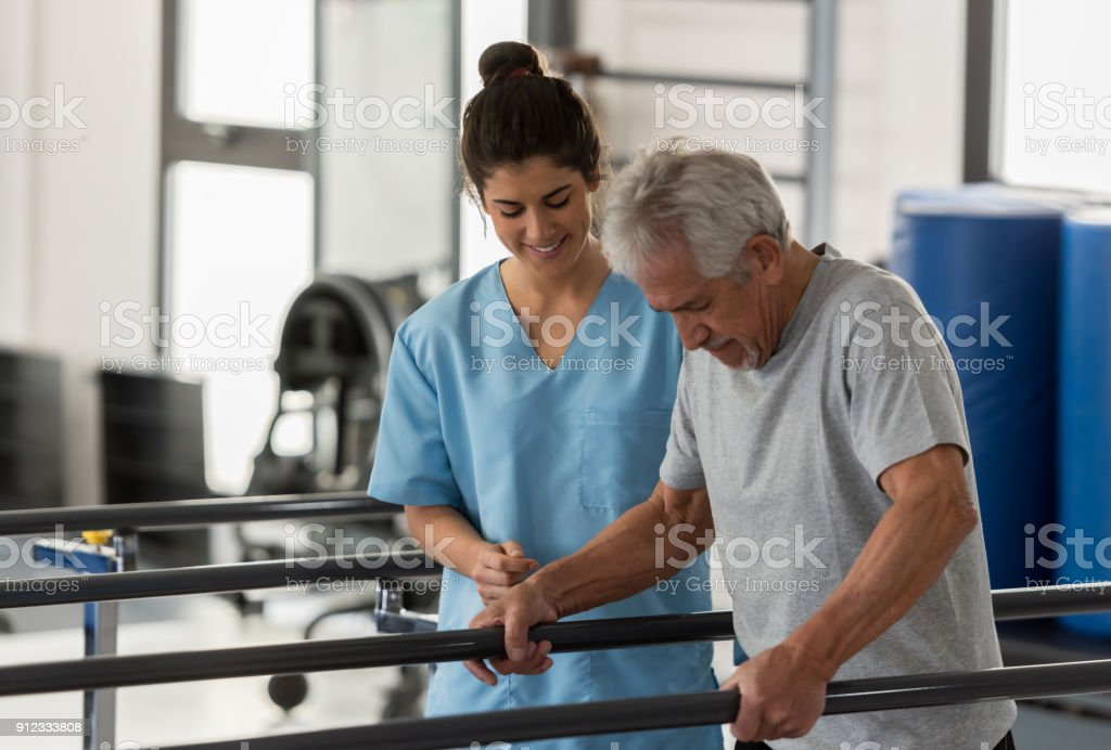 Physiotherapist helping a senior patient while he walks using his hands to support his weight on the bars stock photo