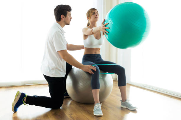 Physiotherapist helping patient to do exercise on fitness ball in physio room. Shot of physiotherapist helping patient to do exercise on fitness ball in physio room. sports medicine stock pictures, royalty-free photos & images