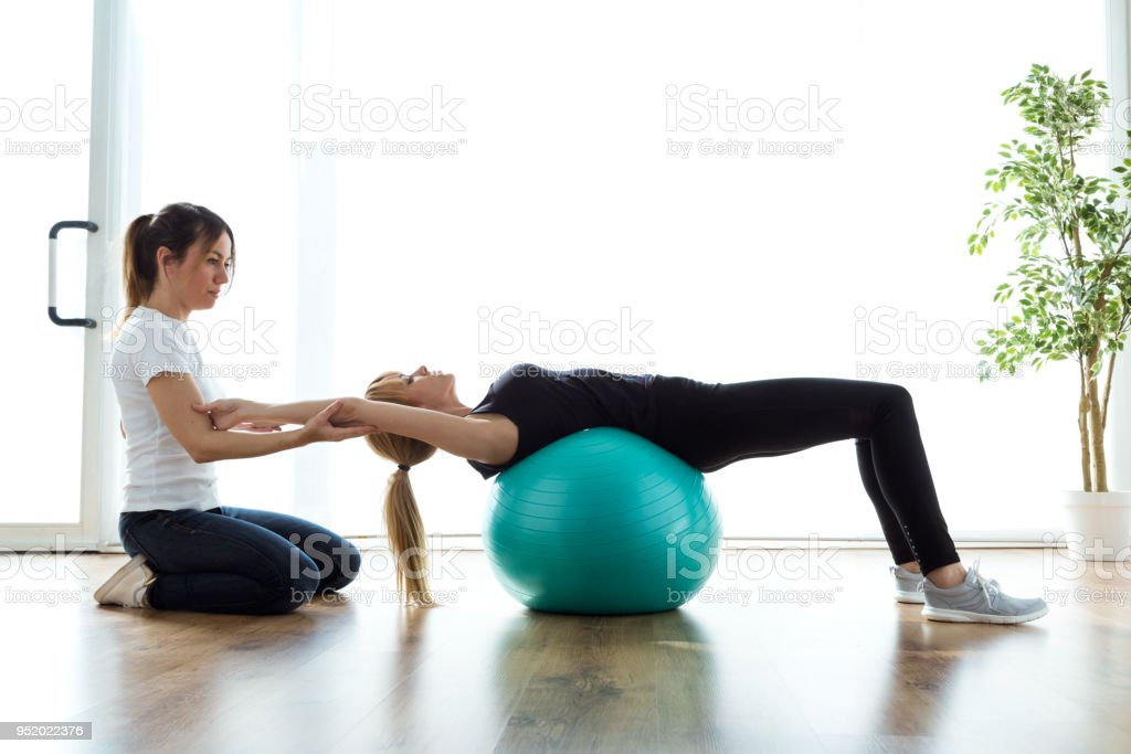 Physiotherapist helping patient to do exercise on fitness ball in physio room. stock photo