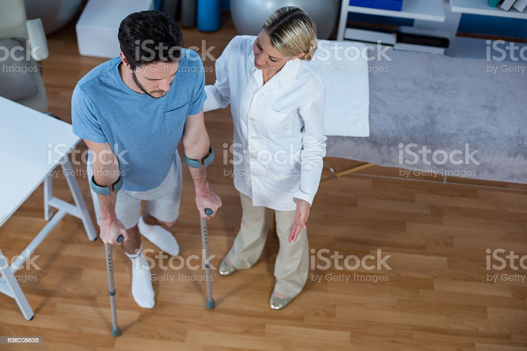 Physiotherapist helping patient to walk with crutches stock photo