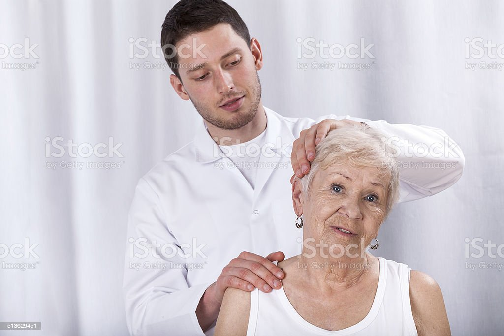 Physiotherapist helping patient with neck ache stock photo