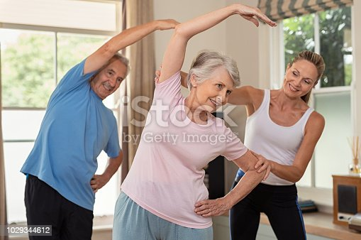 942580016istockphoto Physiotherapist helping senior couple exercise 1029344612