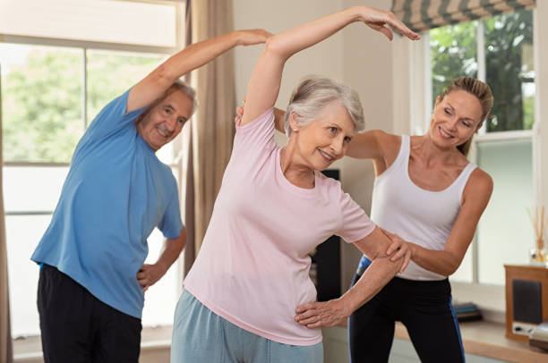 physiotherapist helping senior couple exercise - relaxation exercise stock pictures, royalty-free photos & images