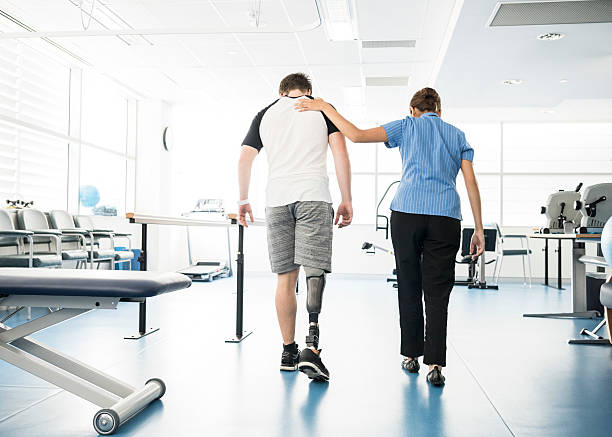 physiotherapist helping young man with prosthetic leg - australian nurses stock photos and pictures