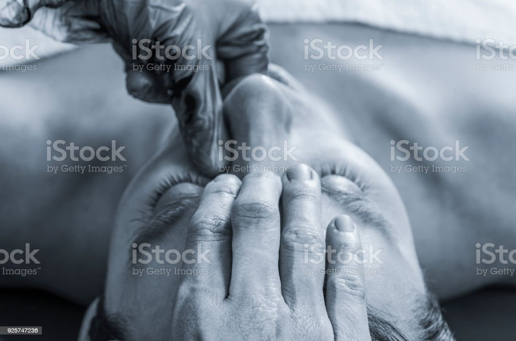 Physiotherapist is doing intraoral technique of massage masseter muscle. Osteopathy stock photo