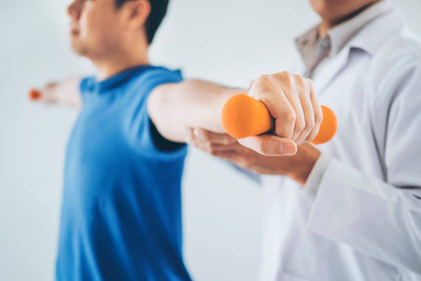 physiotherapist man giving exercise with dumbbell treatment about arm and shoulder of athlete male patient physical therapy concept - sports medicine stock pictures, royalty-free photos & images