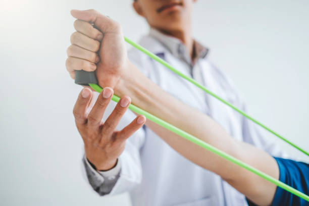 physiotherapist man giving resistance band exercise treatment about chest muscles and shoulder of athlete male patient physical therapy concept - medicina sportiva foto e immagini stock