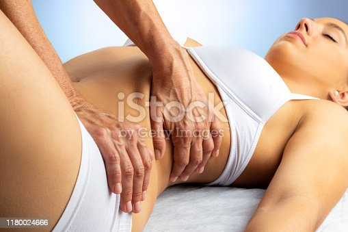 istock Physiotherapist manipulating torso and hip on young woman. 1180024666