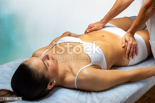 istock Physiotherapist manipulating young woman's hips. 1180025875