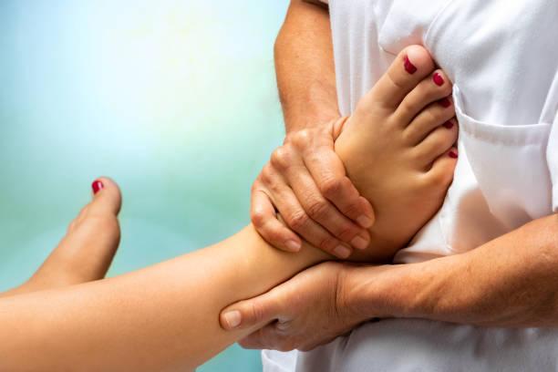 Physiotherapist massaging human foot stock photo
