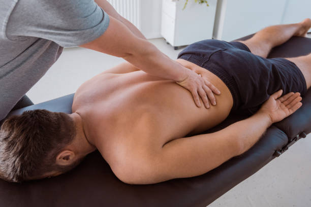 physiotherapist massaging the back of the man - medicina sportiva foto e immagini stock