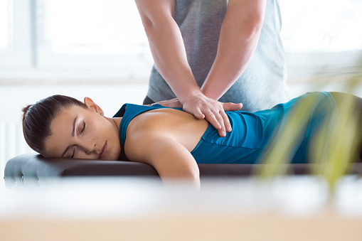 Massage therapist giving back massage to young woman. Patient lying on massage table.