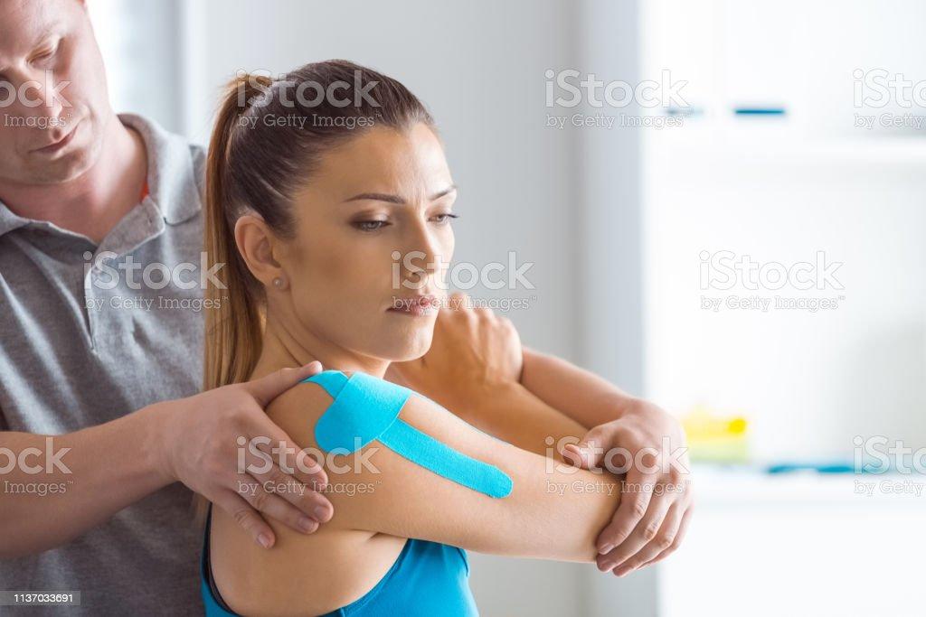 Physiotherapeutin massiert junge Frau - Lizenzfrei Allgemeinarztpraxis Stock-Foto