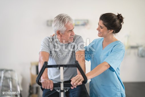 istock Physiotherapist motivating a senior man on a static bycicle looking at each other smiling 912333852