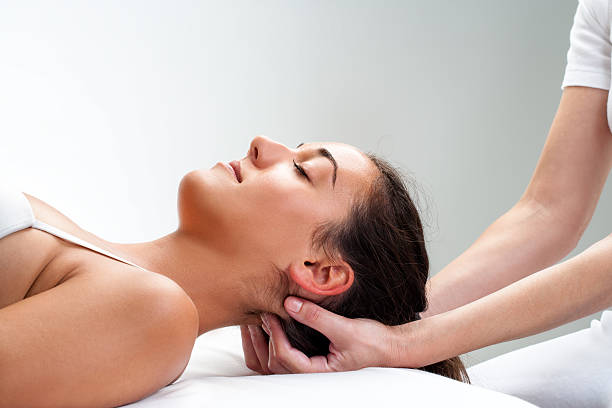 Physiotherapist pressing back of womans head. Close up of  chiropractor pressing back of woman's head. Therapist doing healing massage with fingers at back of neck. osteopathy stock pictures, royalty-free photos & images