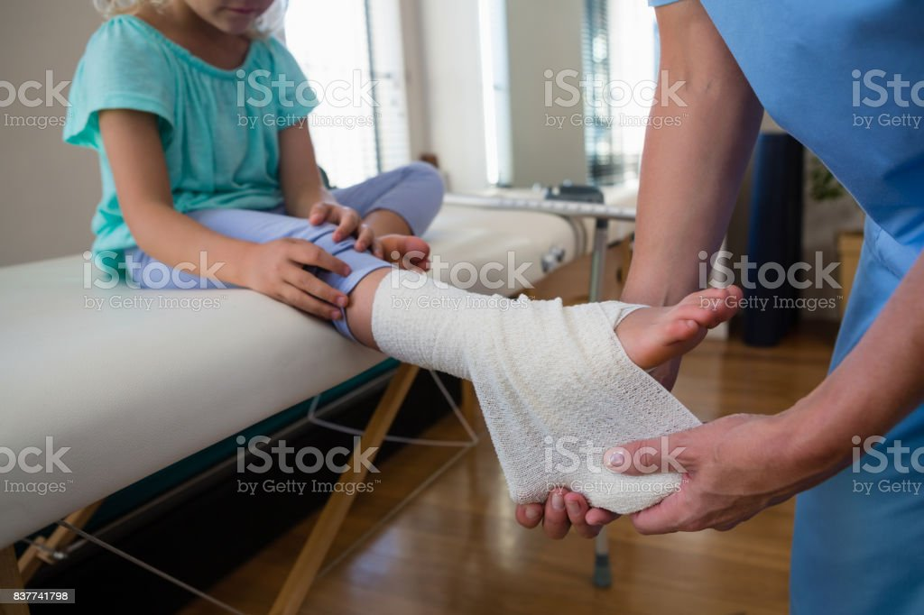 Physiotherapist putting bandage on injured feet of girl patient in...