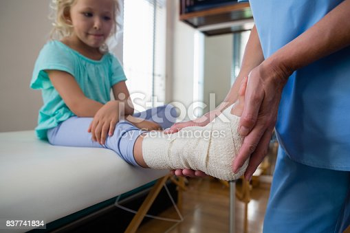 istock Physiotherapist putting bandage on injured feet of girl patient 837741834