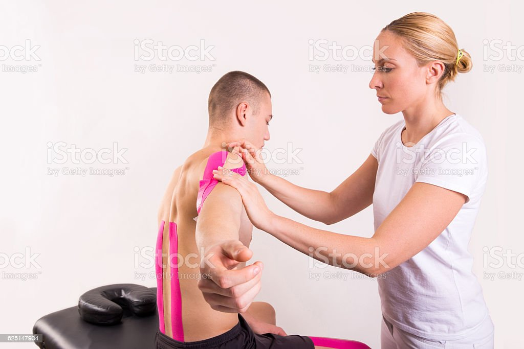 physiotherapist putting kinesio tape stock photo