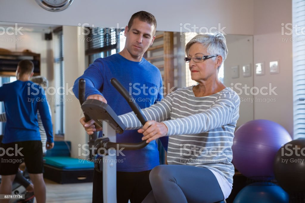 Physiotherapist showing workout record on exercise bike stock photo
