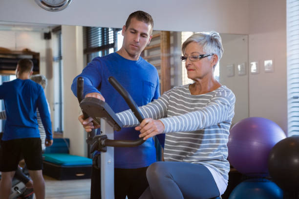 Physiotherapist showing workout record on exercise bike Physiotherapist showing workout record on exercise bike in clinic physiology stock pictures, royalty-free photos & images