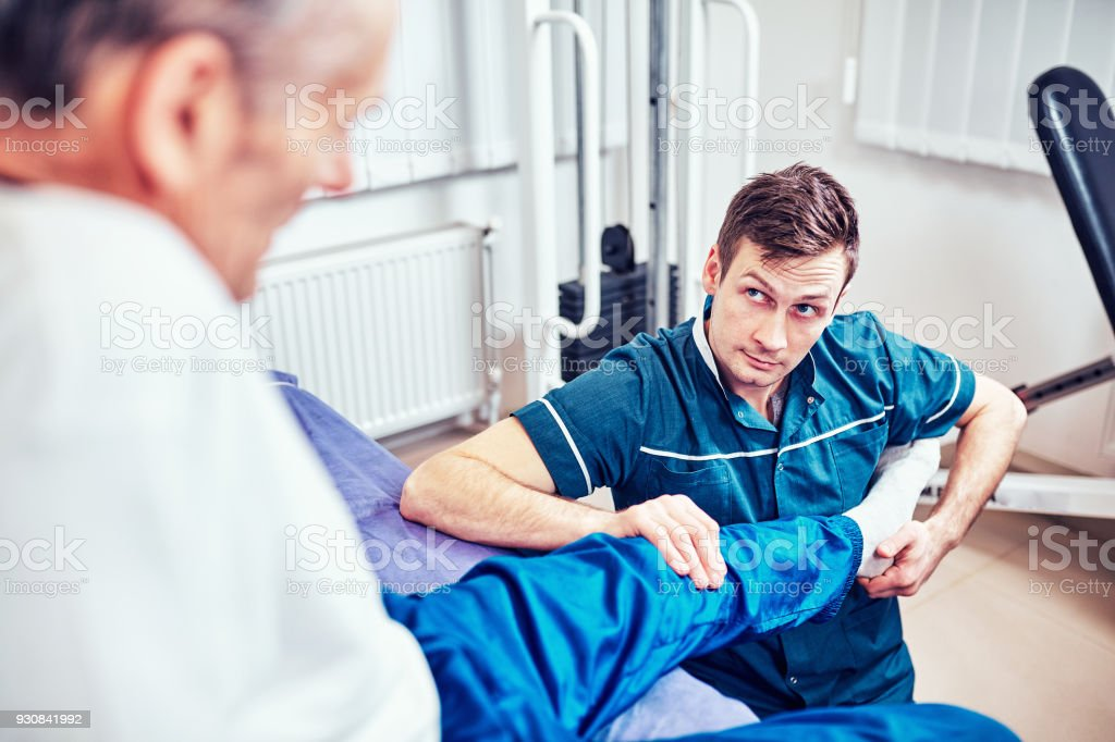 Physiotherapist treating a patient in a patient's office stock photo