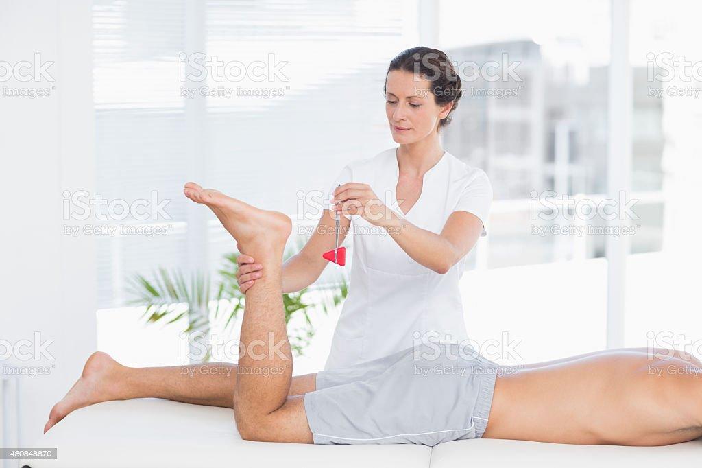 Physiotherapist using reflex hammer stock photo