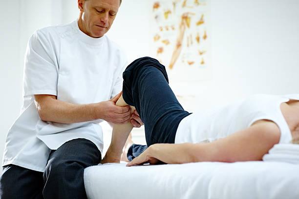 Physiotherapist working on woman's lower leg stock photo