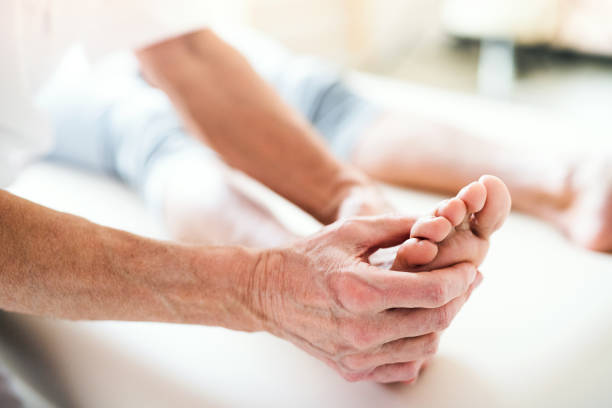 a physiotherapist working with a patient. - old man feet stock photos and pictures