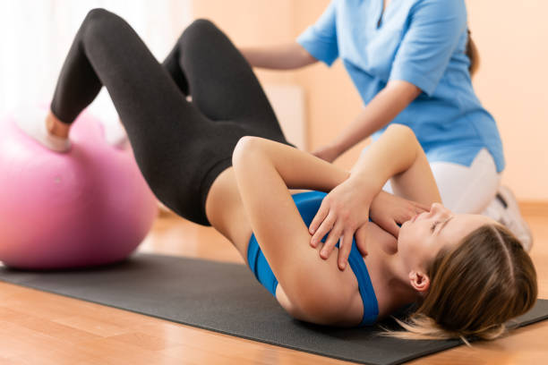 Physiotherapist working with young female client on core strength using fitball. Rehabilitation and physiotherapy background. Physiotherapist working with young female client on core strength using fitball. Rehabilitation and physiotherapy background. sports medicine stock pictures, royalty-free photos & images