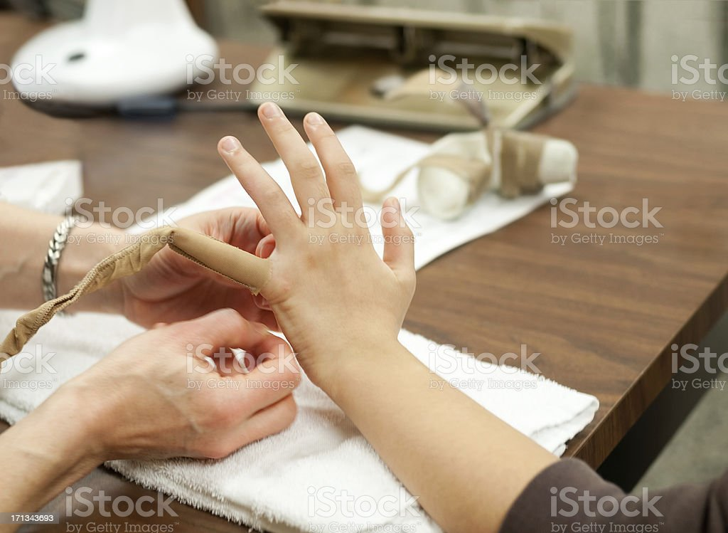 Physiotherapist Wrapping Patient's Finger to Control Swelling stock photo