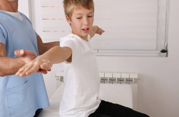 Physiotherapy for school boy , Children Poor Posture Correction, Scoliosis examination . Kinesiology treatment Physiotherapy for school boy , Children Poor Posture Correction, Scoliosis examination . Kinesiology treatment sports medicine stock pictures, royalty-free photos & images