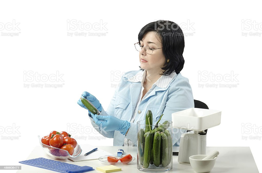 Phytosanitary technician measuring length of cucumber royalty-free stock photo