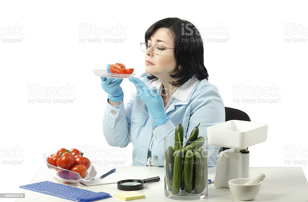 Phytosanitary technician smelling tomato halves royalty-free stock photo