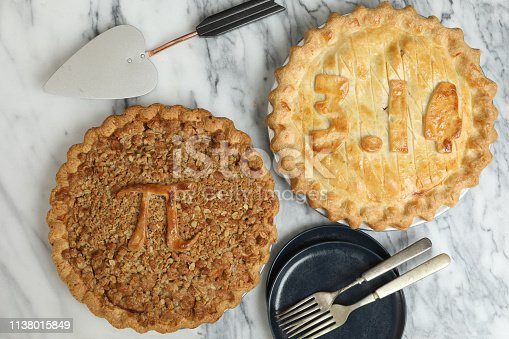 An overhead close up horizontal photograph of two Pi Pies, one displays the π symbol itself and the other one shows the value of 3.14. The pies were baked to commemorate March the 14th as Pi Day.