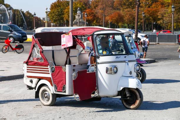 Piaggio Ape Calessino Paris, France - September 15, 2019: Touristic three-wheeled tuktuk Piaggio Ape Calessino in the city street. three wheel motorcycle stock pictures, royalty-free photos & images