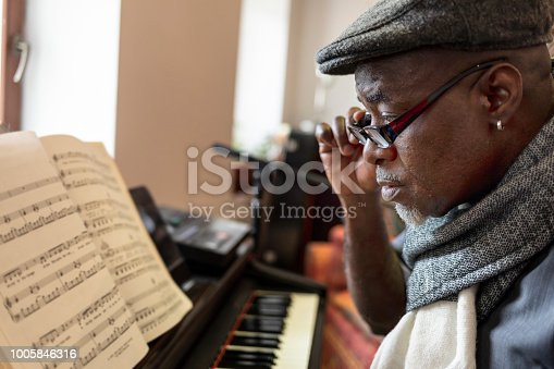 Mature african pianist looking at notebook in studio.