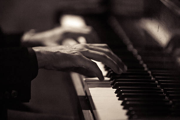 Pianist Black and white close up shot of an unrecognizable man playing the piano. pianist stock pictures, royalty-free photos & images