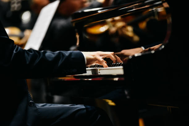 Pianist playing a piece on a grand piano at a concert, seen from the side. Pianist playing a piece on a grand piano at a concert, seen from the side. pianist stock pictures, royalty-free photos & images