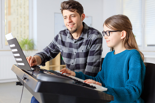 Pianist Showing Sheet To Girl While Training Stock Photo - Download Image Now