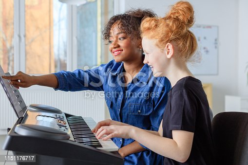 Smiling teacher showing sheet while teaching piano to female student. Pre-adolescent girl is learning music in class. They are in casuals at conservatory.