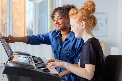 Pianist Showing Sheet While Teaching Girl In Class Stock Photo - Download Image Now