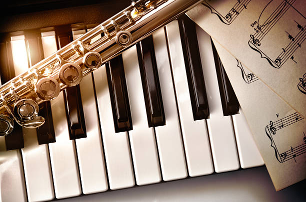 piano and flute with golden shine and sheet music top - classical stock photos and pictures