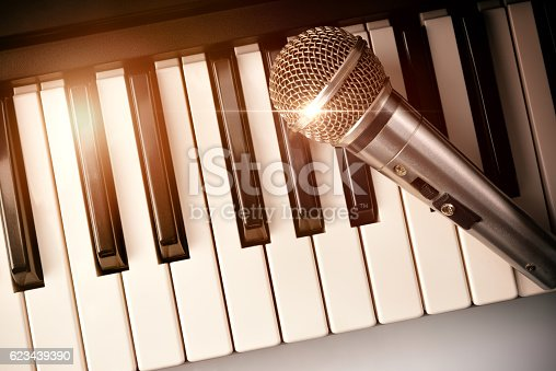 istock Piano and microphone with golden sparkles top view 623439390
