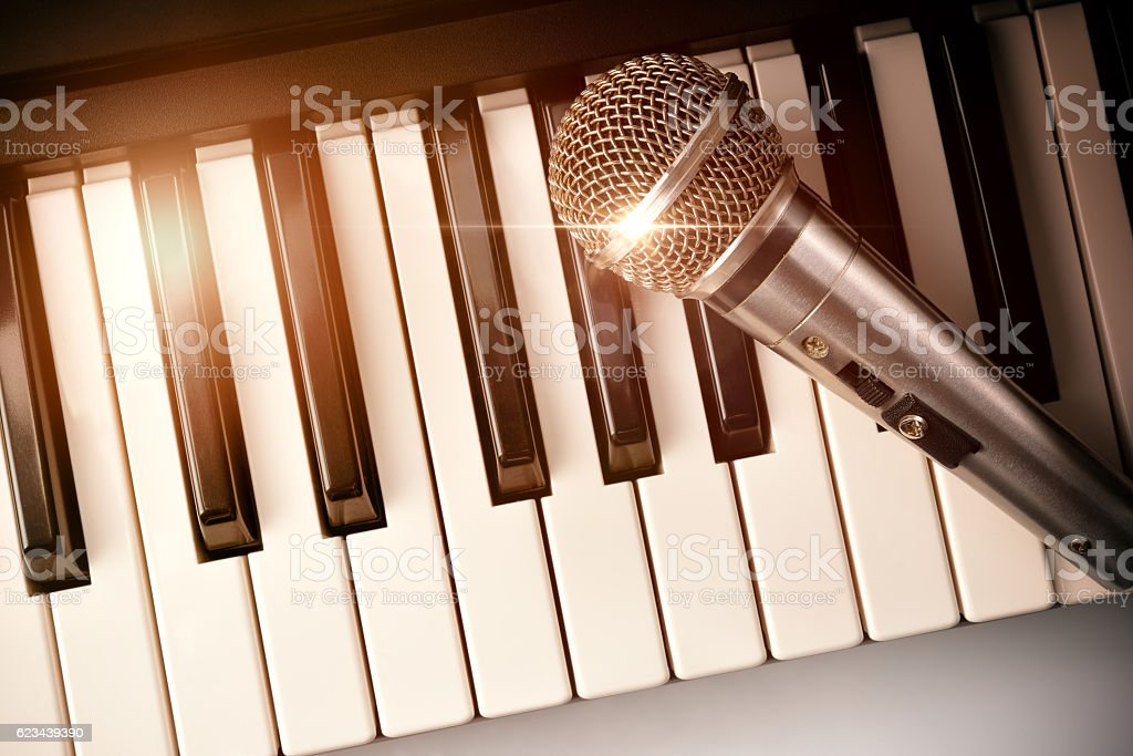 Piano and microphone with golden sparkles top view stock photo