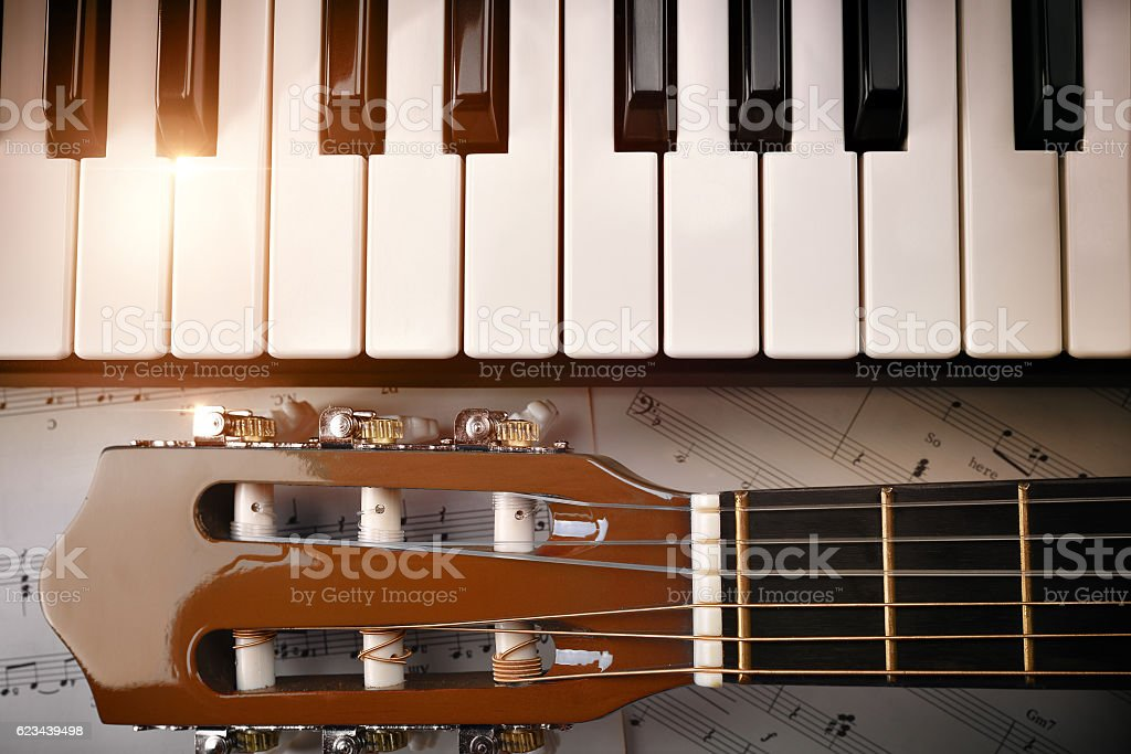 Piano and tuning peg guitar and sheet music background top stock photo