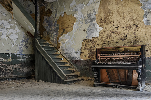Piano by a staircase in an old decayed room