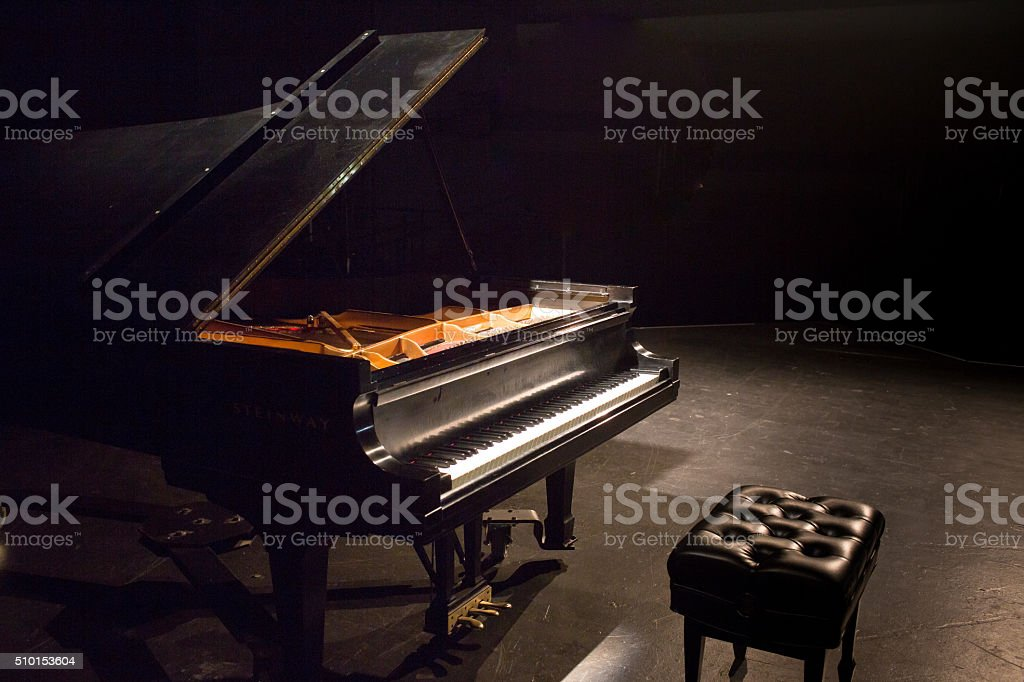 piano on concert stage with music background and lights